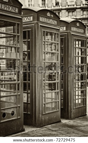 Vintage sepia image of three iconic London phone booths - stock photo