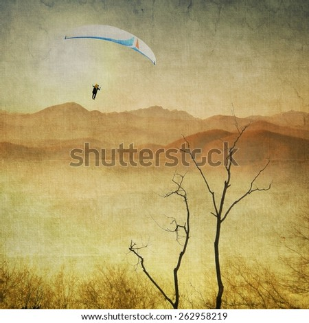 Vintage sepia landscape with paragliding in flight - stock photo