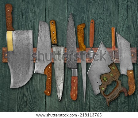 vintage set of knives on the magnet rack against wall - stock photo