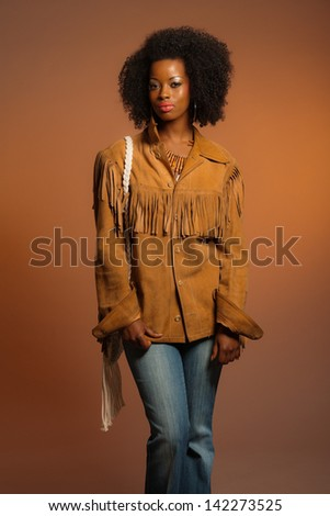 Vintage seventies fashion african woman with brown leather jacket. Brown background.