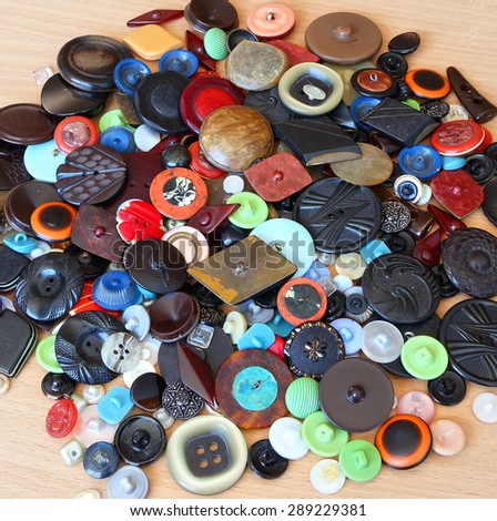 Vintage sewing buttons on wood background - stock photo