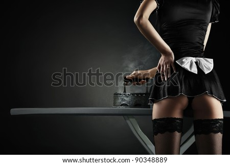 Vintage sexy maid with  retro iron on black background - stock photo