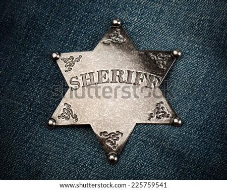 Vintage sheriff star badge on blue denim background - stock photo