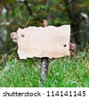 vintage signboard with paper for text in a forest - stock photo