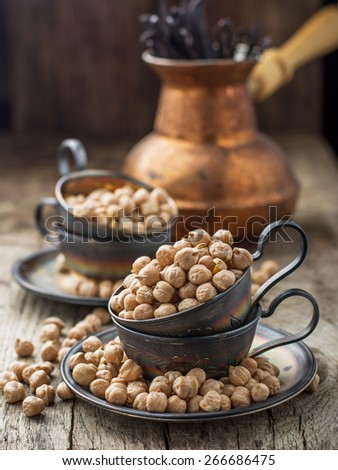 Vintage silver cup filled with dry chickpeas on a dark wooden background. selective Focus - stock photo