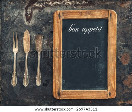 Vintage silver cutlery and blackboard. Retro style toned picture. Sample text bon appetit. - stock photo