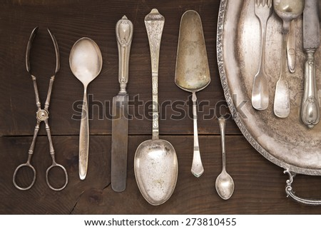 Vintage silver cutlery on a wooden background - stock photo