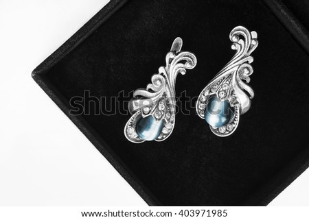 Vintage silver earrings in black jewel box closeup as a background - stock photo