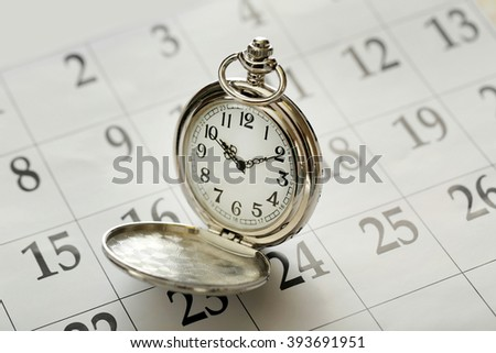 Vintage silver pocket watch laying on calender page with dates, close up - stock photo