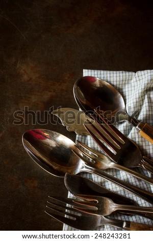 Vintage silverware on rustic grunge tray - stock photo
