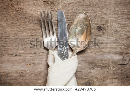 Vintage silverware on rustic wooden table. Top view.