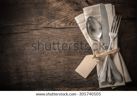 Vintage silverware with an empty tag on rustic wooden background - stock photo