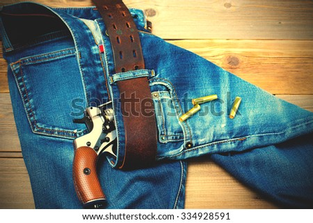vintage silvery revolver nagant with cartridges in old blue jeans, close up. instagram image filter retro style - stock photo