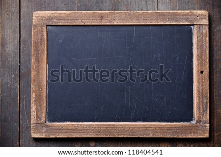 Vintage slate chalk board on wooden background - stock photo