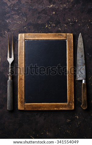 Vintage slate chalk board template menu and meat fork and kitchen knife on dark background - stock photo