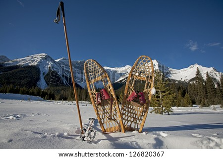 vintage snowshoes and bamboo ski poles in winter landscape with snowy mountains and blue skies in the background