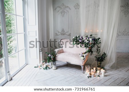 Vintage Sofa Of Soft Pink Color, Decorated With Flowers And Greens, Stands  In A
