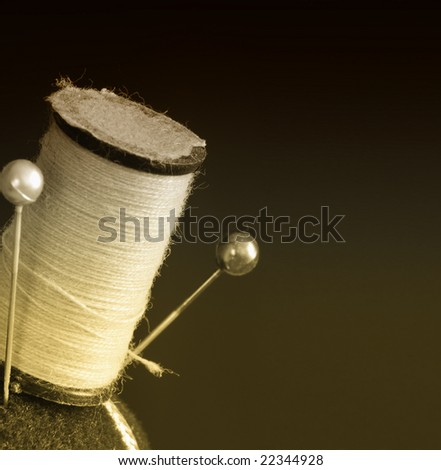 Vintage spool of thread and pins on a pin cushion in sepia, macro shot - stock photo