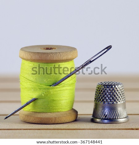 Vintage spool of thread with needle closeup. Tailor's work table, textile or fine cloth making. - stock photo
