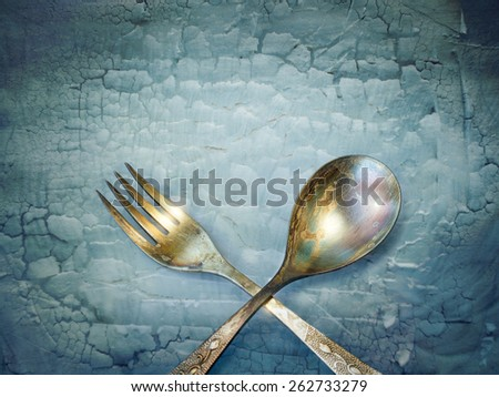 Vintage spoon and fork on grunge background