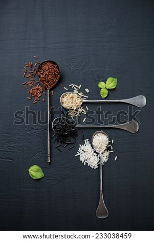 Vintage spoons with red, brown, white and black rice, above view - stock photo