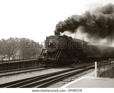 Vintage steam engine locomotive speeding on railroad tracks curve and blowing heavy black smoke while pulling an antique passenger train in nostalgic sepia - stock photo