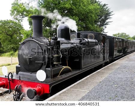 Vintage steam engine or locomotive; steam engine stationary at rural train station  - stock photo