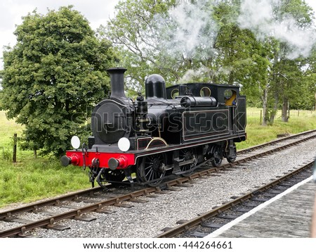 Vintage steam engine or locomotive; steam engine stationary in countryside - stock photo