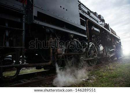 vintage steam locomotive heading towards sunset - stock photo