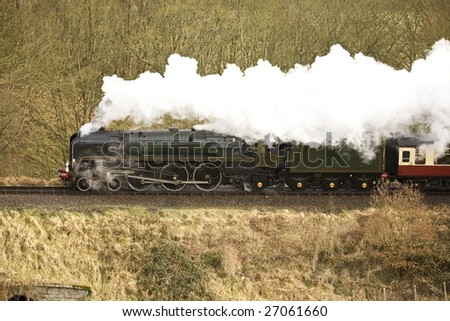 vintage steam traim with identification markings removed powering through countryside - stock photo