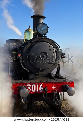 Vintage steam train makes steam alongside platform at railway station - stock photo