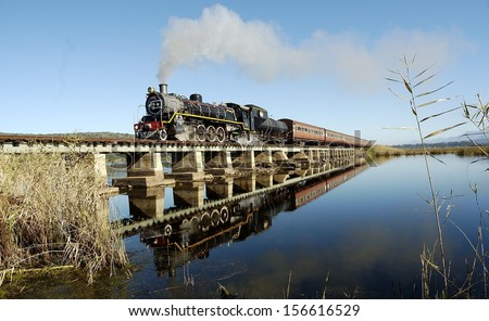 Vintage steam train on a bridge Traveling Between George And Knysna, Garden Route, South Africa - stock photo