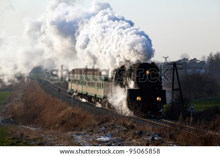 Vintage steam train passing through countryside, wintertime - stock photo