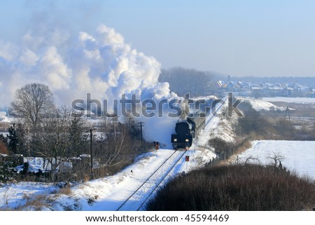 Vintage steam train passing through snowy countryside - stock photo