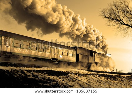 Vintage steam train puffing through countryside during wintertime