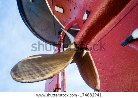 Vintage Steam Tug Brass Propeller Vessel Mounted dry-docked old steam tug boat vessel with solid brass propeller and riveted hull metal plates visible in its construction early 1950's - stock photo
