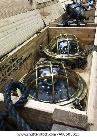 Vintage steel and glass industrial light bulbs laid in an old wooden case in a warehouse.