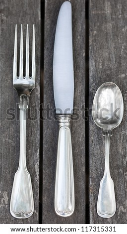 Vintage sterling silver knife, fork and spoon on a rustic weathered table.  Close up view of texture and details. Pattern is called French Thread or Fiddle Thread - stock photo
