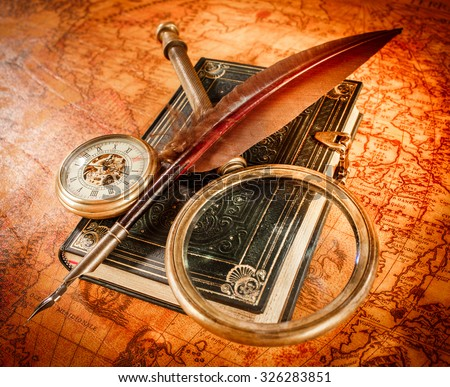 Vintage still life - magnifying glass, pocket watch, old book and goose quill pen lying on an old map in 1565. - stock photo