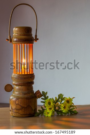 vintage still life of burning candle and  flower on table wood
