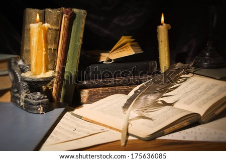 Vintage still life. Old books and candles on wooden table on dark background - stock photo