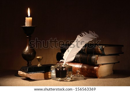 Vintage still life. Old inkstand near lighting candle and books - stock photo