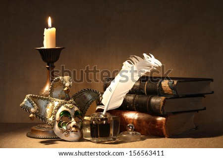 Vintage still life. Old inkstand near lighting candle and venetian mask - stock photo
