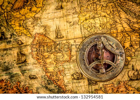 Vintage still life. Vintage compass lies on an ancient world map of 1565. - stock photo