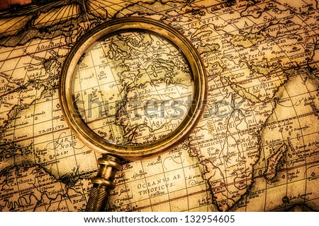 Vintage still life. Vintage magnifying glass lies on an ancient world map - stock photo