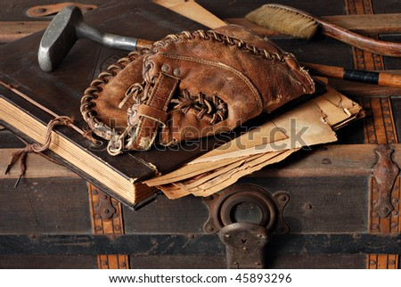 Vintage still life with antique baseball glove, golf club and scrapbook on rustic old steamer trunk. - stock photo