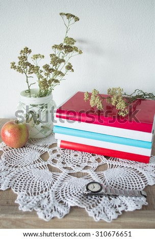 Vintage still life with books, watches, apple and vase with flowers on doily