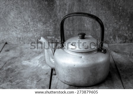 Vintage still life with Kettle on wooden background.black and white - stock photo