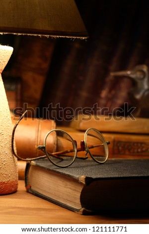 Vintage still life with old spectacles on book near desk lamp - stock photo