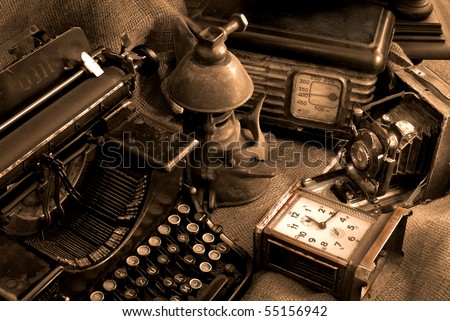 Vintage still life with old typewriter, retro camera and radio receiver in brown colors - stock photo